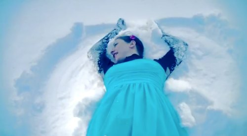 Image of Karyn Ellis making a snow angel. Screenshot #1 from the music video.